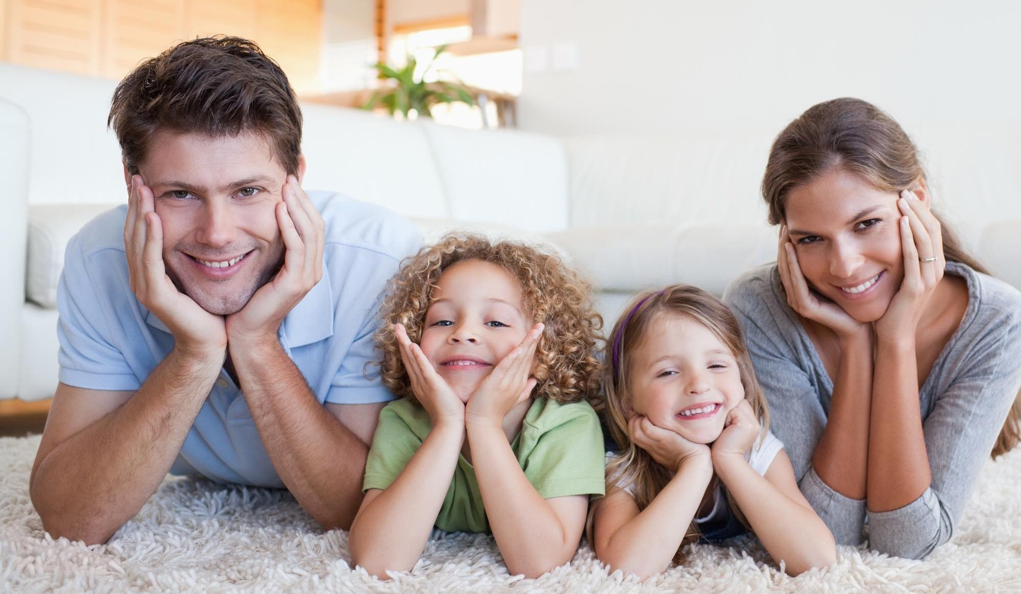 Family lying on a carpet in their living room